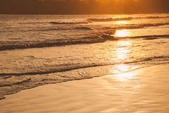 Coucher du soleil sur la plage tropicale dans Sri Lanka - la couleur d'or ondule l'eau de mer illuminée par le soleil photographie stock libre de droits