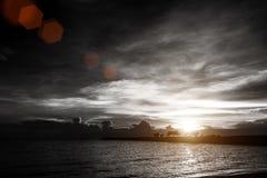 Coucher du soleil sur le ciel nuageux à la plage de mer avec le pont de roche de silhouette Images libres de droits