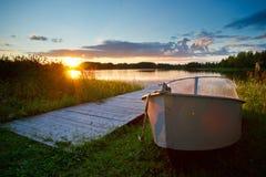 Coucher du soleil sur le lac, bateau de pêche sur le rivage photo stock