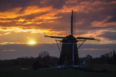 Coucher du soleil sur le moulin à vent néerlandais photo libre de droits