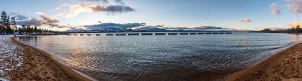 Coucher du soleil sur le rivage du lac Tahoe du sud, sierra crêtes de montagne couvertes dans la neige évidente à l'arrière-plan, image stock