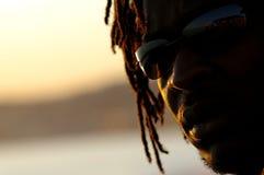 Coucher du soleil sur les lunettes de soleil s'usantes d'un homme Photographie stock libre de droits