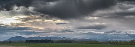 Coucher du soleil sur un ciel dramatique de nuages au-dessus d'un pré et d'une petite forêt de pin avec des collines à l'arrière- images stock