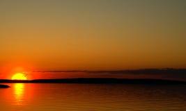 Coucher du soleil sur un lac et le silouette de la mouette Photo stock