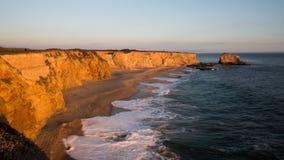 Coucher du soleil sur une plage avec de hautes falaises Image stock
