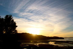 Coucher du soleil sur une plage d'or reculée de baie Photographie stock
