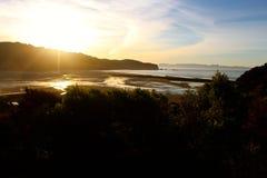 Coucher du soleil sur une plage d'or reculée de baie Photos stock