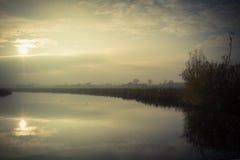 Coucher du soleil sur une rivière avec un ciel légèrement opacifié Photo stock