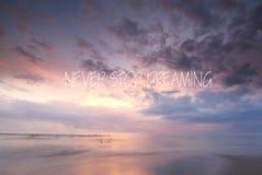 Coucher du soleil trouble sur la plage avec la citation inspirée - ne cessez jamais de rêver photographie stock libre de droits