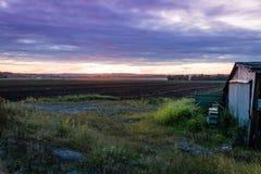 Coucher du soleil ultra-violet dramatique d'été au-dessus de ferme et d'hutte Photo stock