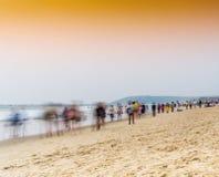 Coucher du soleil vibrant vif horizontal sur la plage indienne avec la foule du pe images stock