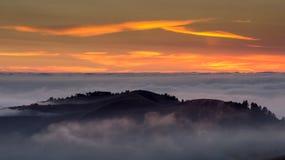 Coucher du soleil vif d'été dans Santa Cruz Mountains avec le brouillard brumeux et les cieux oranges Images libres de droits