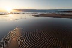 Coucher du soleil vif rouge à la mer baltique avec le miroir comme l'eau - sable et vagues à nervures - Veczemju Klintis, Letto photo libre de droits