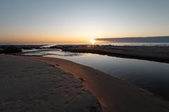 Coucher du soleil vif rouge à la mer baltique avec le miroir comme l'eau - Veczemju Klintis, Lettonie - 13 avril 2019 photo stock