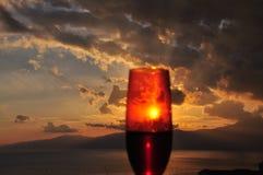 Coucher du soleil vu du verre de vin rouge Photographie stock