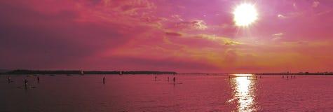 Couchers du soleil au-dessus des paddlebroaders Photographie stock