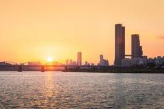 Couchers du soleil derrière les gratte-ciel du yeouido et des ponts à travers Images stock