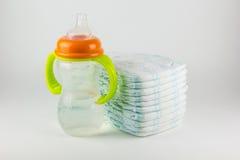 Couches-culottes et bouteille de bébé sur un fond blanc Image libre de droits