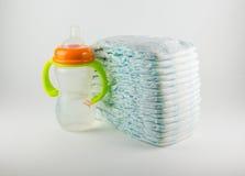 Couches-culottes et bouteille de bébé sur un fond blanc Photographie stock libre de droits