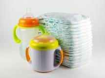 Couches-culottes et bouteilles de bébé sur un fond blanc Photographie stock
