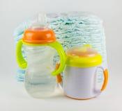 Couches-culottes et bouteilles de bébé sur un fond blanc Image stock