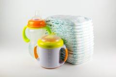 Couches-culottes et bouteilles de bébé sur un fond blanc Photo libre de droits