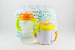 Couches-culottes et bouteilles de bébé sur un fond blanc Image libre de droits
