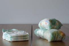 Couches-culottes nouvelles et utilisées de bébé sur le fond en bois de table photo libre de droits