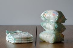 Couches-culottes nouvelles et utilisées de bébé sur le fond en bois de table image libre de droits