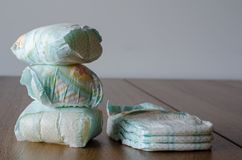 Couches-culottes nouvelles et utilisées de bébé sur le fond en bois de table copie photo libre de droits