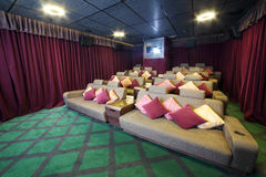 Couches with cushions and projector in small movie theate Royalty Free Stock Images