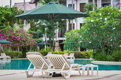 Couches with umbrellas around the pool Stock Photo