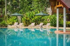 Couches with umbrellas around swimming pool. In the resort Stock Images