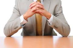 Coudes d'homme d'affaires sur des mains de bureau pliées Photographie stock