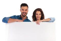 Coudes de penchement de couples occasionnels heureux sur le conseil vide Images libres de droits