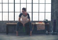 Coudes de repos de femme sur des genoux tout en se reposant sur le banc dans le gymnase de grenier Image stock