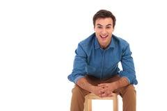 Coudes de repos de sourire d'homme occasionnel sur des genoux tout en se reposant Image libre de droits