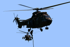 Cougar and Apache. Air Mobile Troops exit Cougar via rope while being covered by an Apache helicopter Royalty Free Stock Image