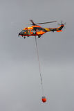 Cougar helicopter bambi bucket. TORREJON, SPAIN - OCT 11, 2014: Spanish Air Force Eurocopter Cougar helicopter with a bambi bucket filled with water, used for Royalty Free Stock Images