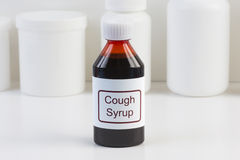 Cough Mediciine. Cough medicine in amber bottle with white conatiners in background Stock Images
