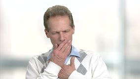 Cough of middle aged man, slow motion. Mature man in sweater coughing on blurred background. Sick adult man stock video