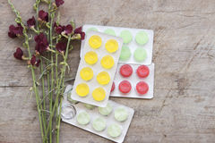 Cough sore throat pastille colorful and flowerw on table Royalty Free Stock Photos