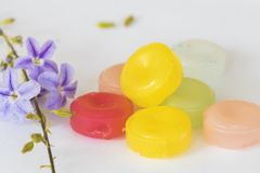 Cough sore throat pastille colorful pills. From herbal with purple flower arrangement on background white wooden Royalty Free Stock Photography