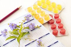 Cough sore throat pastille colorful pills. From herbal with purple flower on background white wooden Stock Photo
