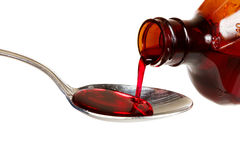 Cough syrup. A bottle of cold medicine poured into a spoon Stock Image