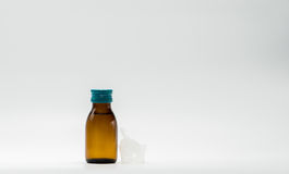 Cough syrup in amber bottle with blank label and a plastic measuring cup, teaspoon Stock Image