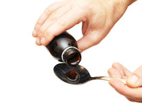 Cough syrup poured into a spoon Royalty Free Stock Images
