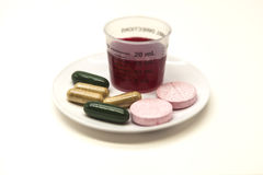 The cough syrup and tablets on the small plates, the prescription for the patient. Royalty Free Stock Images