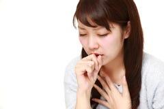 Coughing  japonés joven de la mujer Imagen de archivo libre de regalías