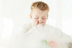 Coughing boy surrounded by dangerous chemicals Royalty Free Stock Photo